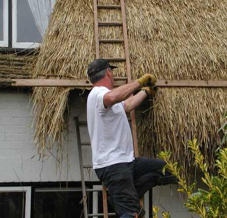 Brian cutting the thatch